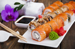 Sushi. Different Sushi rolls,wasabi and ginger on a plate on wooden background stock images