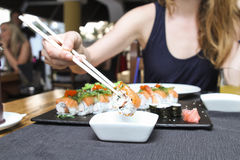 Sushi dipping in a soya sauce. Model woman dipping sushi roll in a  soya sauce  with sushi set on a plate Stock Image