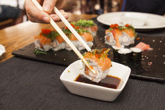 Sushi dipping in a soya sauce. Dipping sushi roll in a  soya sauce  with sushi set on a plate Stock Photos