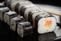 Sushi rolls on black dish Royalty Free Stock Photo