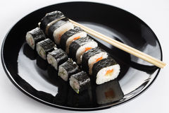 Sushi rolls on black dish Stock Photos