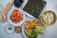 Sushi - diversos ingredientes en las placas alistan y se prepararon Foto de archivo libre de regalías