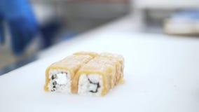 Sushi do corte do cozinheiro chefe em um restaurante filme
