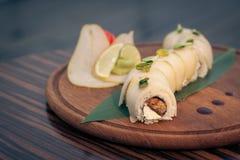 Sushi do dragão com a pera na tabela de madeira; foto de stock