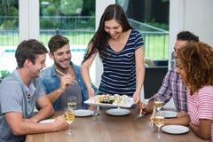 Sushi do serviço da mulher aos amigos ao beber o vinho Foto de Stock