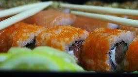 Sushi do wasabi do gengibre e rolos japoneses frescos, varas de madeira chinesas macro video estoque