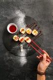 Sushi doux avec de la confiture de fraise rouge d'un plat noir photographie stock libre de droits