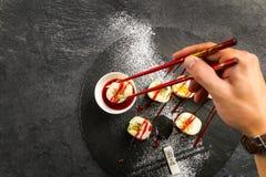 Sushi doux avec de la confiture de fraise rouge d'un plat noir Image stock