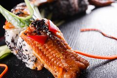 Sushi dragon with eel, cucumber and avocado on a black background. Japanese food, tasty of meal for lunch.  stock photos