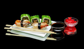 Sushi e rolos em uma placa em um fundo preto Imagens de Stock