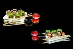 Sushi e rolos em uma placa em um fundo preto Fotos de Stock