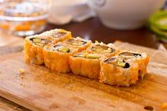 Sushi e rolos japoneses com salmões, abacate, pepino e flyi imagem de stock royalty free