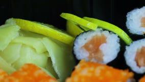 Sushi e rolos japoneses frescos do wasabi do gengibre, sashimi macro, uramaki e nighiri Prato japonês típico filme