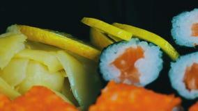 Sushi e rolos japoneses frescos do wasabi do gengibre, sashimi macro, uramaki e nighiri Prato japonês típico vídeos de arquivo