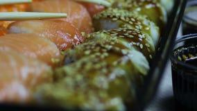 Sushi e rolos japoneses frescos, sashimi macro, uramaki e nighiri Prato japonês típico video estoque