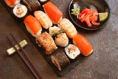 Sushi e rotoli di sushi, nigiri dei sushi sul piatto di pietra Immagini Stock
