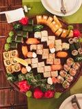 Sushi eingestellt auf Holztisch mit grünen Servietten Lizenzfreie Stockfotos