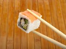 Sushi em chopsticks de madeira Foto de Stock