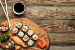 Sushi en broodjes met gekruiste stokken worden geplaatst die Stock Afbeelding