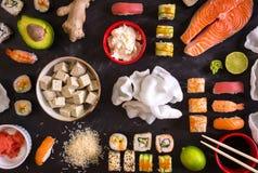 Sushi en ingrediënten op donkere achtergrond Stock Foto