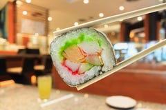 Sushi en palillos con el interior del restaurante japonés Foto de archivo libre de regalías