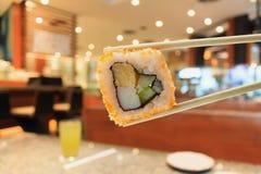 Sushi en palillos con el interior del restaurante japonés Imagenes de archivo
