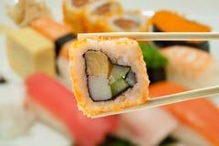 Sushi en palillos con el sushi de la falta de definición Fotos de archivo libres de regalías