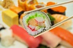 Sushi en palillos con el sushi de la falta de definición en fondo de la placa Fotos de archivo