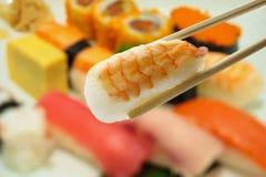 Sushi en palillos con el sushi de la falta de definición en fondo de la placa Fotos de archivo libres de regalías