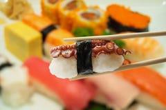 Sushi en palillos con el sushi de la falta de definición en fondo de la placa Foto de archivo libre de regalías