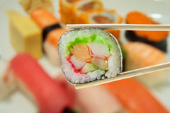 Sushi en palillos con el sushi de la falta de definición en una placa Imagen de archivo