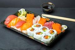 Sushi en Sashimibroodjes op een zwarte steen slatter Verse gemaakte die sushi met zalm, garnalen, wasabi en gember worden geplaat Royalty-vrije Stock Afbeelding
