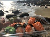 Sushi en tailandés en la palma de una mujer contra el mar y la costa costa por la tarde imágenes de archivo libres de regalías
