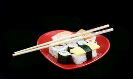 Sushi en un fondo negro con los palillos Imagen de archivo