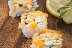 Sushi en una placa de madera Imagen de archivo