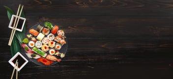 Sushi en una superficie de madera negra Fotografía de archivo libre de regalías