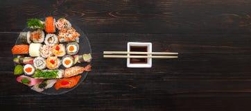 Sushi en una superficie de madera negra Foto de archivo libre de regalías