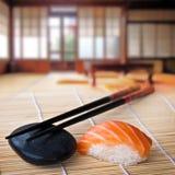 Sushi et baguettes saumonés, intérieur japonais Images stock