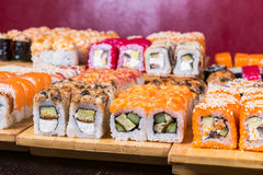 Sushi et petits pains assortis sur le conseil en bois dans la lumière foncée Photos stock