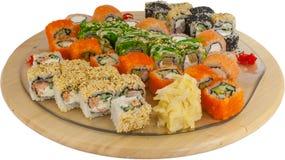 Sushi et petits pains assortis sur un conseil en bois Photographie stock libre de droits