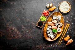 Sushi et petits pains d'un plat avec du riz bouilli en cuvette et baguettes photographie stock libre de droits