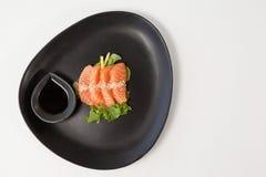 Sushi för fyra sashimi tjänade som med soya i svart platta Royaltyfri Bild