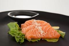Sushi för fyra sashimi tjänade som med soya i svart platta Royaltyfri Fotografi