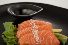Sushi för fyra sashimi tjänade som med soya i svart platta Arkivfoto