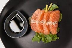 Sushi för fyra sashimi tjänade som med soya i svart platta Fotografering för Bildbyråer
