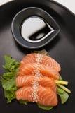 Sushi för fyra sashimi tjänade som med soya i svart platta Arkivfoton