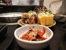 Sushi förläggas på tabellen fotografering för bildbyråer