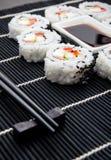 Sushi fijado en la estera del bambú negro Foto de archivo