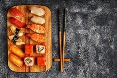 Sushi fijado: sushi y rollos de sushi en la placa de madera Fotos de archivo libres de regalías