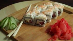 Sushi freschi, rotoli sulla tavola Fondo scuro Bastoni dei sushi archivi video